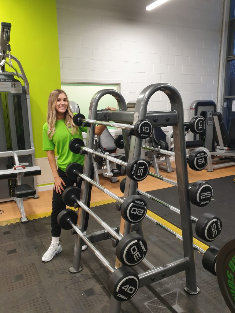 girl standing by gym weights