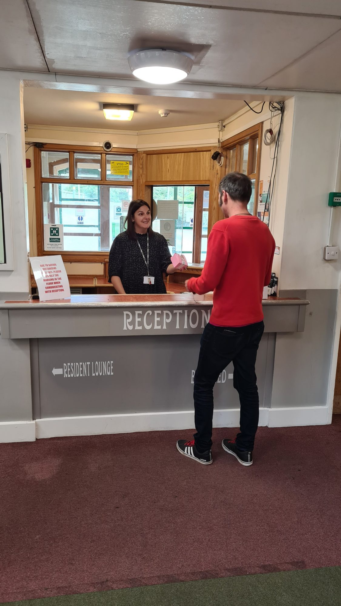 man and woman talking at reception desk