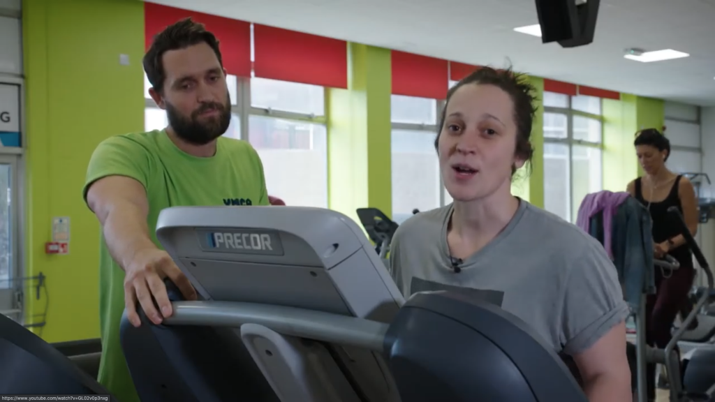 woman on a treadmill with instructor next to her